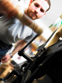 Tamarind Master Printer Lee Turner, cranking the press.